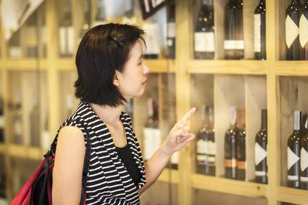 Asian woman choosing for wine at liquor store   photo