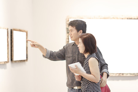 Happy couple asian looking at modern painting in art gallery  photo