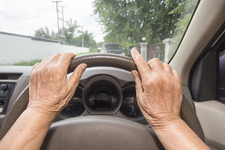 despacio: Mujer mayor que conduce un coche poco a poco a la zaga