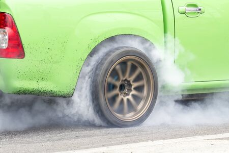 race car burns rubber off its tires in preparation for the race photo