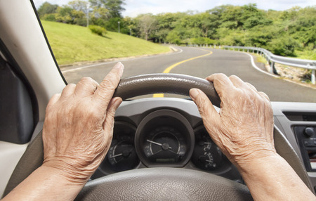steering: Senior woman driving a car slowly on highway  Stock Photo