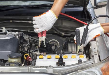car battery: mechanic working in auto repair shop   Stock Photo
