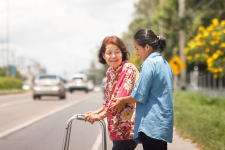 年配の女性、ウォーカーを使用して通りを横切る