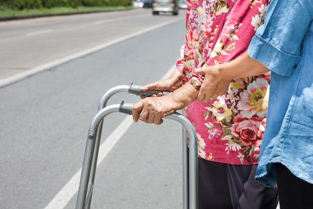 hinder: senior woman using a walker cross street