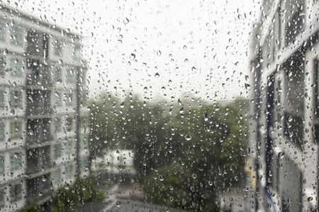 kropla deszczu: Krople deszczu na szybie okna, budynki w tle.