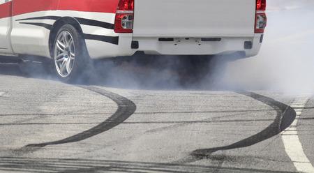 huellas de neumaticos: Rueda de frenado de emergencia con humo en la carretera.