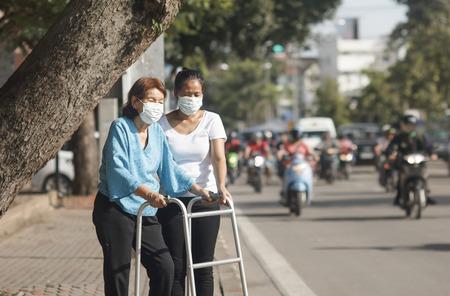 staub: ältere Frau mit Maske für schützen die Luftverschmutzung in der Innenstadt