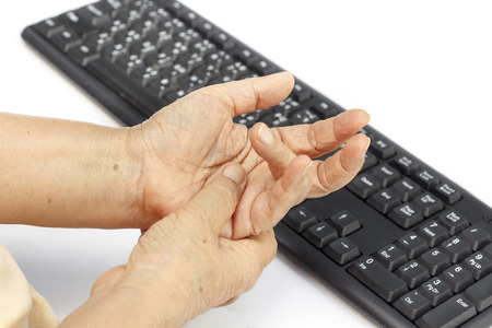 finger on trigger: Senior woman painful finger due to prolonged use of keyboard and mouse.
