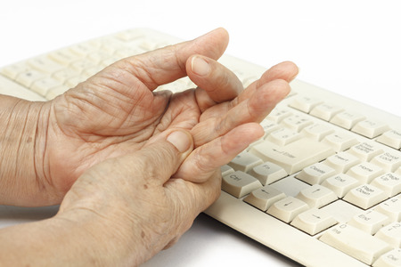 Senior woman painful finger due to prolonged use of keyboard and mouse. Banco de Imagens - 33116997