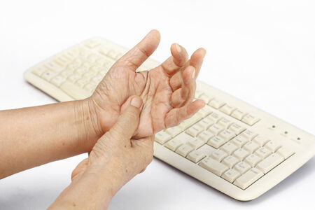 carpal: Senior woman painful finger due to prolonged use of keyboard and mouse.