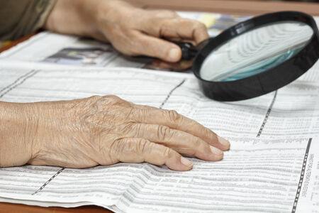 Senior woman reading stock listings photo
