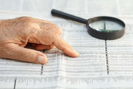listings: Senior woman reading stock listings