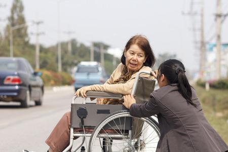 senior woman using a wheelchair to cross street 版權商用圖片 - 36308778