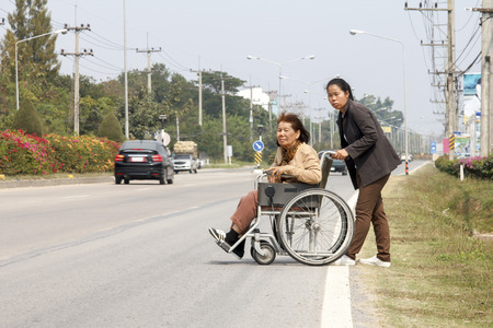 senior woman using a wheelchair cross street