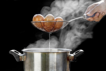 stainless steel pot: boiling eggs in stainless steel pot Stock Photo