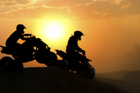 Silhouette ATV or Quad bikes Jump in the sunset. photo