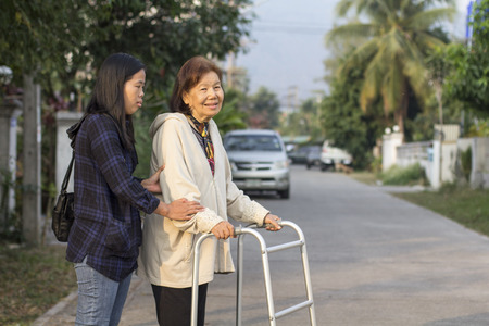 mobility nursing: senior woman using a walker cross street
