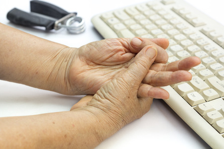 gatillo: Mujer mayor dedo dolorosa debido al uso prolongado del teclado y el ratón.