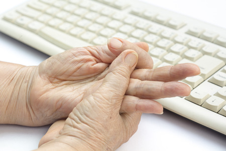 paralysis: Senior woman painful finger due to prolonged use of keyboard and mouse.