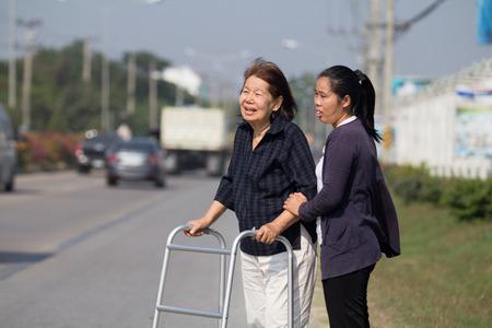 hinder: enior woman using a walker cross street