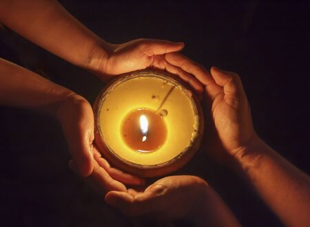 rituals: Candle in the hands together Stock Photo