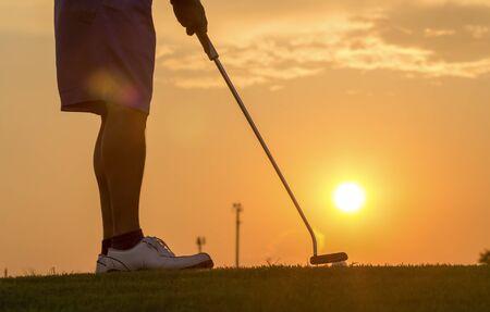 Man putting golf ball against sunset