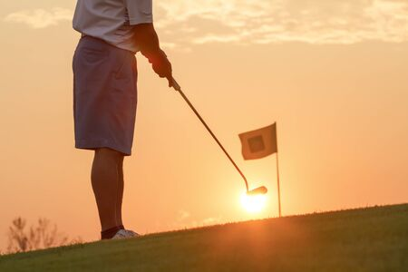 golf swing: Man putting golf ball against sunset