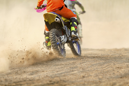 Motocross racer accelerating speed in track photo