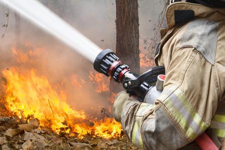 blasting: firefighters spray water to bushfire