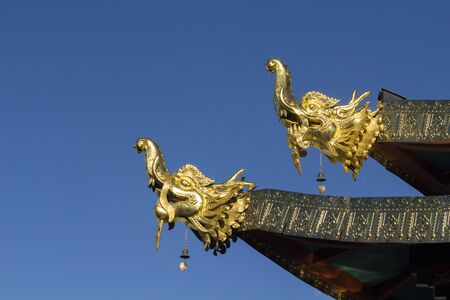 protector: Tibetan style sculpture. Head of makara, a mythical sea dragon acts as protector on the roof of the Temple, Shangri-La, Yunnan, China. Stock Photo