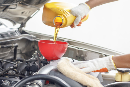 Car mechanic pouring new oil to engine.