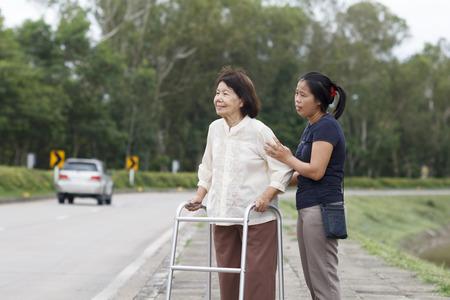 senior vrouw met behulp van een rollator dwarsstraat Stockfoto