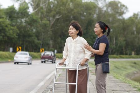 cross roads: senior woman using a walker cross street
