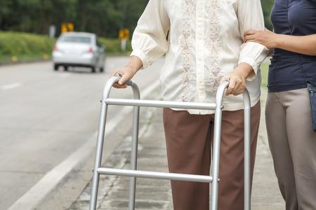 通りを横切る年配の女性が歩行器を使用