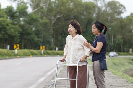 disable: senior woman using a walker cross street