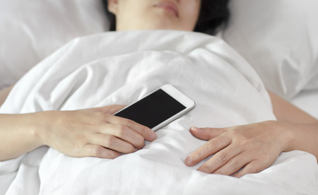 cell phone addiction: Woman sleeping in bed and holding a mobile phone.