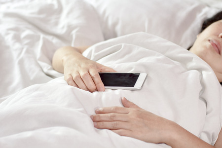 Woman sleeping in bed and holding a mobile phone.