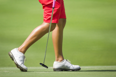 putter: Female golfers walking on green with putter.