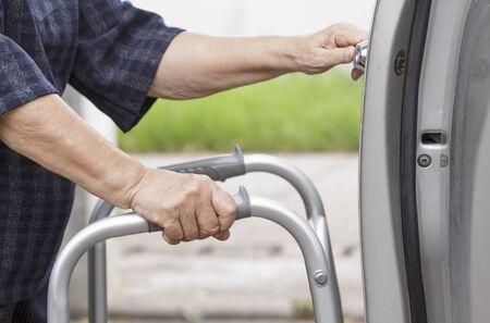 open car door: senior woman open car door with walker at car park