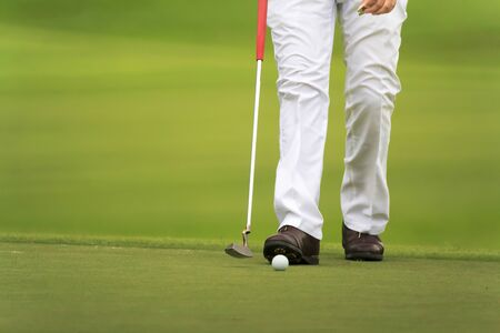 putter: golfers walking on green with putter. Stock Photo