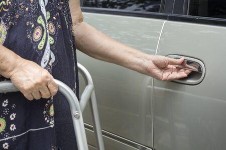 open car door: senior woman open car door with walker on street.