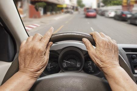 elderly: Senior woman driving a car on street in city.
