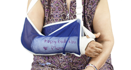 plaster cast: Happy birthday elderly woman with a broken arm on a plaster cast Stock Photo