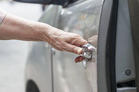 open car door: senior woman open car door