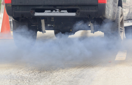 exhaust: Air pollution from vehicle exhaust pipe on road