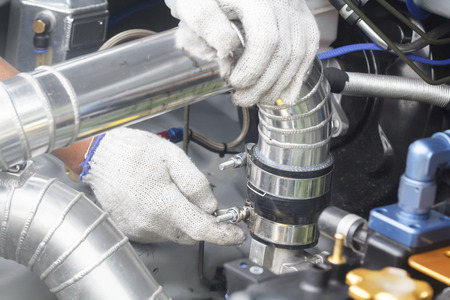 man nuts: Spanner tighten bolt air pipe of engine race car.