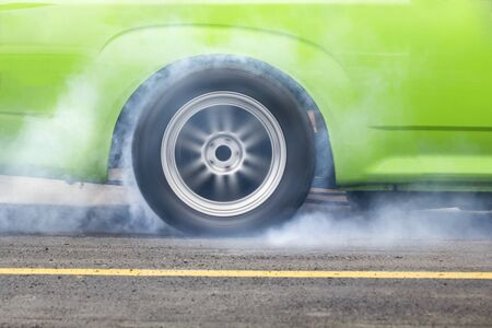 to spin: race car burns rubber off its tires in preparation for the race