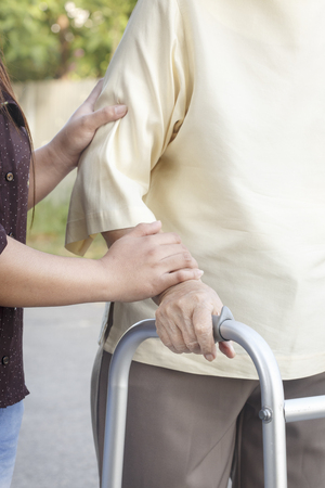 cross street with care: senior woman using a walker with caregiver
