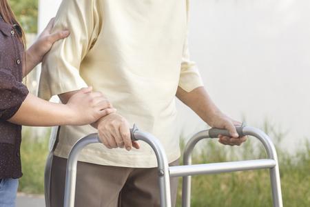 personas enfermas: mujer mayor con un andador con cuidador Foto de archivo