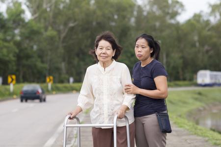 cross street with care: senior woman using a walker cross street